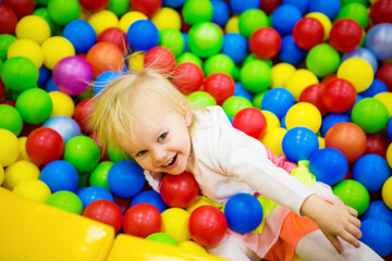 THE BABY IS PLAYING IN COLORED BALLS
