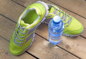 Sports sneakers,  drinking water on a wooden background