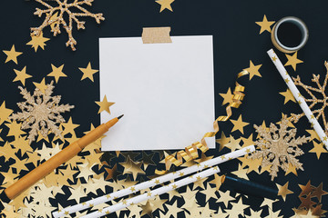 Christmas planning concept mock up. Note on black background with washi tape, gold stars confetti, pen, serpentine and glitter snowflakes. Place for text flat lay