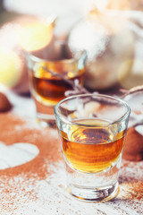 Whiskey or liqueur, truffle chocolate candies in cocoa powder and christmas decorations on white wooden background.