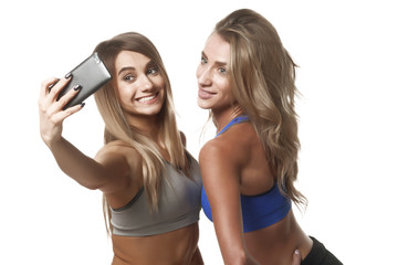 two fitness girls make selfie on white backround isolated