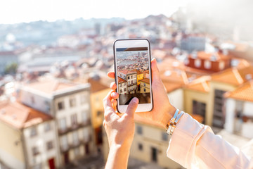 Woman photographing with phone cityscape view on the old town of Porto city in Portugal