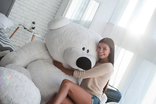 Best friend for a real girl. Beautiful young woman hugging huge teddy bear and looking at camera with smile while sitting indoors