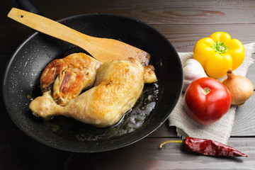 Two roasted chicken legs in black frying pan with vegetables and spices on dark wooden planks close-up view