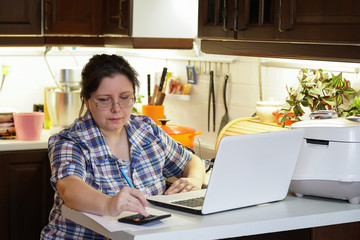 Office in the home kitchen, female entrepreneur.