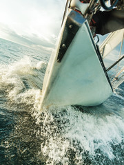 Yachting on sail boat bow stern shot splashing water