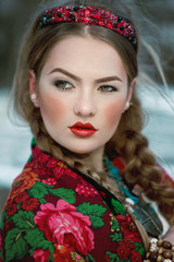 Winter portrait of a young beautiful girl in a colorful scarf in russian style. Vogue boho gipsy fashion style