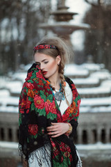 Winter portrait of a young beautiful girl in a colorful scarf in russian style with fountain on the background. Vogue boho gipsy fashion style