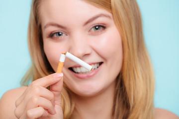 Smilling girl is breaking cigarette