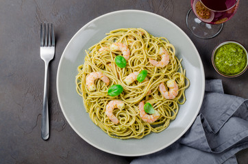 Spaghetti with fried prawns and pesto sauce in a gray plate, red