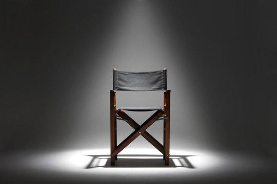 Directors chair against a plain background under a spotlight