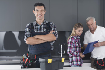 The plumber is posing in the kitchen. He stands cross-arms and smiles.