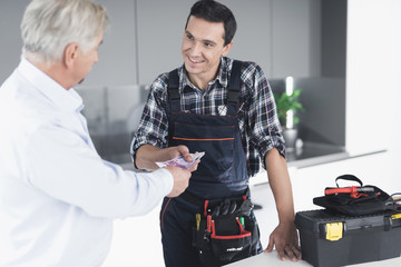 A plumber man communicates with a client who pays for the work done. The old man gives the plumber a fee.