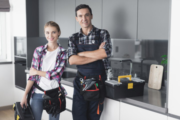 A man and a woman plumber will be cheated in the kitchen. They have just successfully repaired the sink for customer.