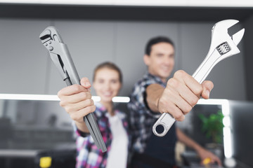 A man and a woman plumber will be cheated in the kitchen. They show the wrenches in the camera.