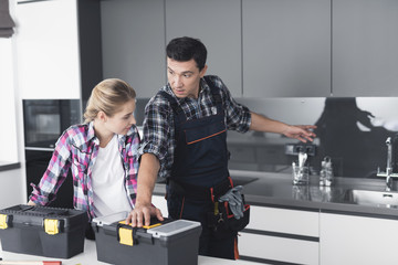 Man and woman in the kitchen of the customer, preparing for the repair work.