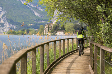 Cyclist along the catwalk of the Toblino lake, in the background the Toblino castle, Valle dei Laghi, Valley of Lakes, Italy
