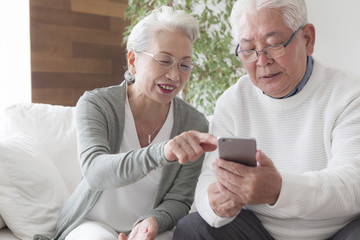 An elderly couple enjoying a smartphone
