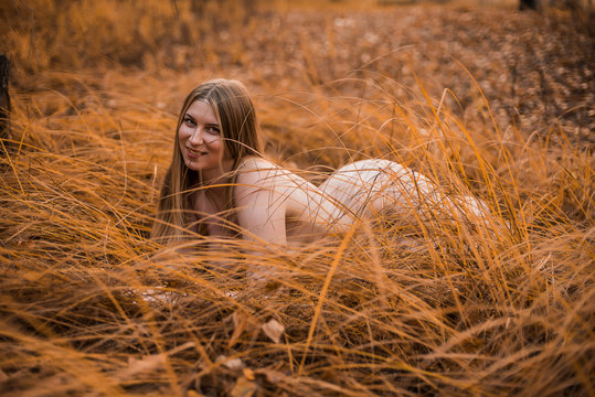 Young, sexy, plump naked girl with really big Breasts lying in the yellow grass in the forest. Autumn, overcast.