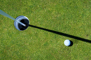 Golf green with golf ball next to the hole, with the flag pole in