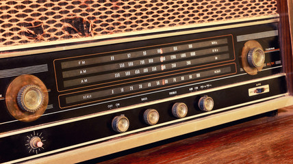 Close-up of vintage radio buttons and tuner control panel. Wooden brown antique retro old radio scale.