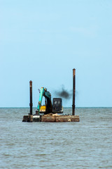 Machines are dredging sand in the sea.