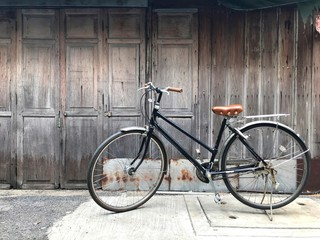 Black bike brown cushion The front door of the house and the old wooden wall is not painted with a simple life concept, exercise, love the world, fresh air, Life slow, travel, economical, healthy