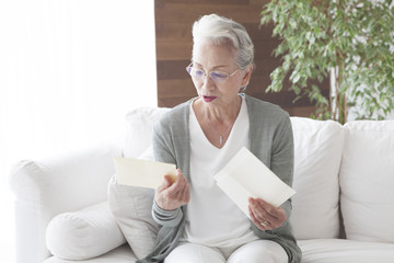 An old lady is reading a letter
