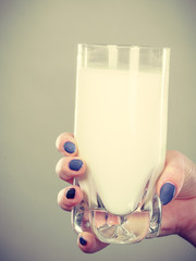 Woman hand holding glass of milk