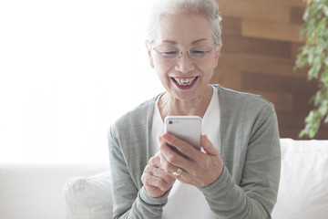An old lady is absorbed in smartphone