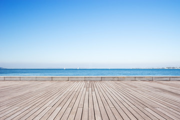 empty wooden floor with blue sea in blue sky