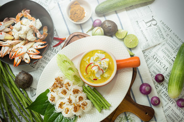 Curry crab, Seafood with Yellow curry sauce in orange ceramic pot, on tablecloths background