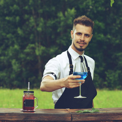 Catering bar service, bartender workplace. Handsome caucasian barman holding wine glass with blue cocktail. Concept of small business, toned image