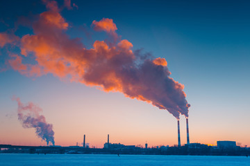 Beautiful winter scenery with smoke coming from power plant chimneys, on a bright, cold, evening. City outskirts industrial landscape.