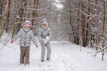 Happy children playing with snow in winter forest, family winter weekend outdoors