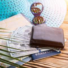 Close-up of travel accessories. Passport, one hundred dollar banknotes, wallet, compass, travel map and blue straw hat on wooden board. Journey through the EU