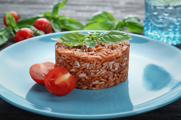 Plate with delicious brown rice on table