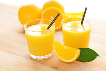 Glasses with yummy fresh orange juice on wooden table
