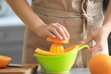 Woman squeezing juice from ripe orange in kitchen