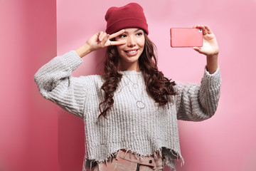 Beautiful hipster girl taking selfie on pink background