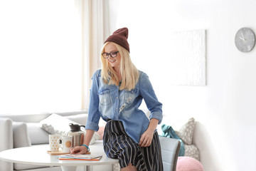 Attractive hipster girl on table at home