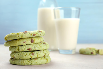 Fresh mint chocolate chip cookies and milk in glassware on table