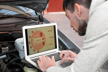Young male mechanic using computer diagnostic while repairing car