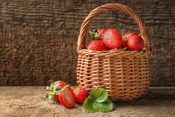 Fresh ripe strawberries in wicker basket on table