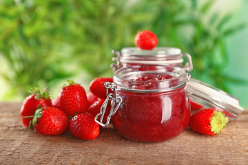 Jar of homemade jam and fresh strawberries on wooden table