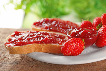 Plate with pieces of bread and strawberry jam on wooden table