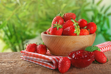 Bowl with fresh strawberries and tasty jam on wooden table