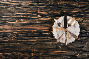 Plate and old cutlery. On a wooden background. Top view. Free space for text.