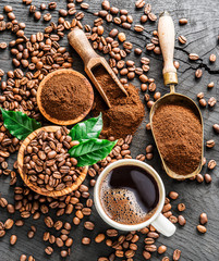 Roasted coffee beans, ground coffee and cup of coffee on wooden table.