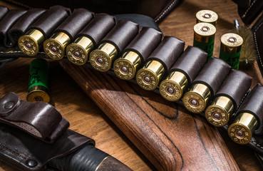 Pump action shotgun, 12 guage cartridge and hunting knife.